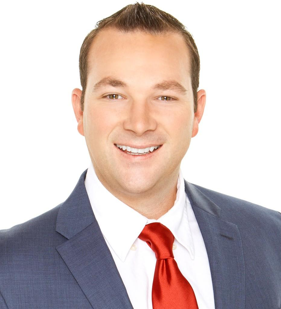 San Diego, A man wears a blue suit, white shirt, and red tie, he smiles