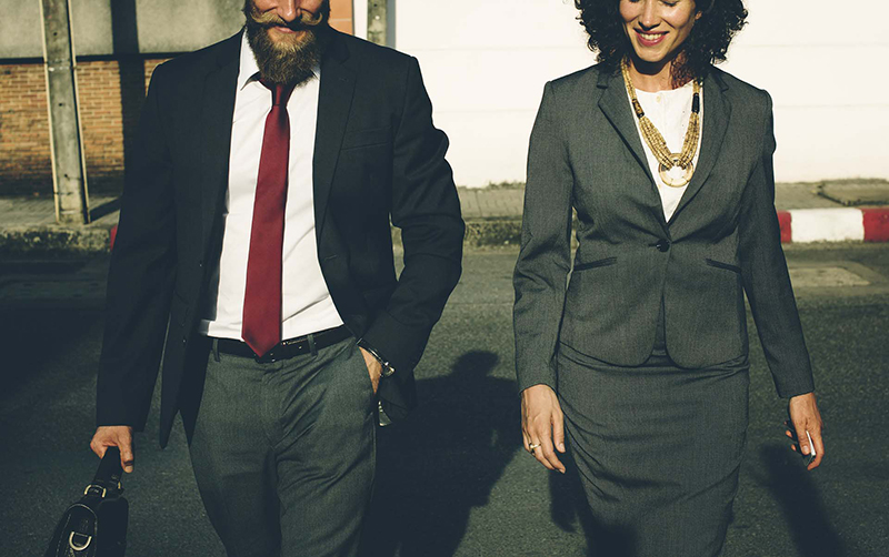 two business professionals, man and woman, walking across street