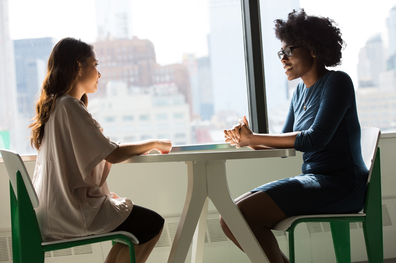 two women talk at a small cafe table, behind them in the window is a view of city buildings
