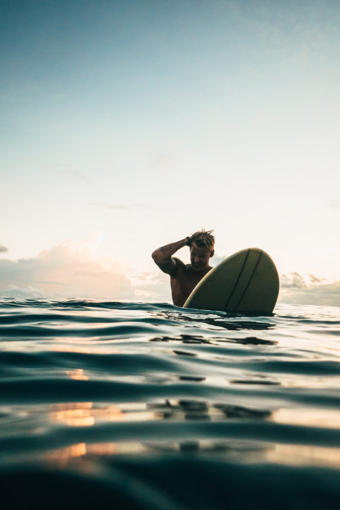 Surfer scratches head as hew wades in the water