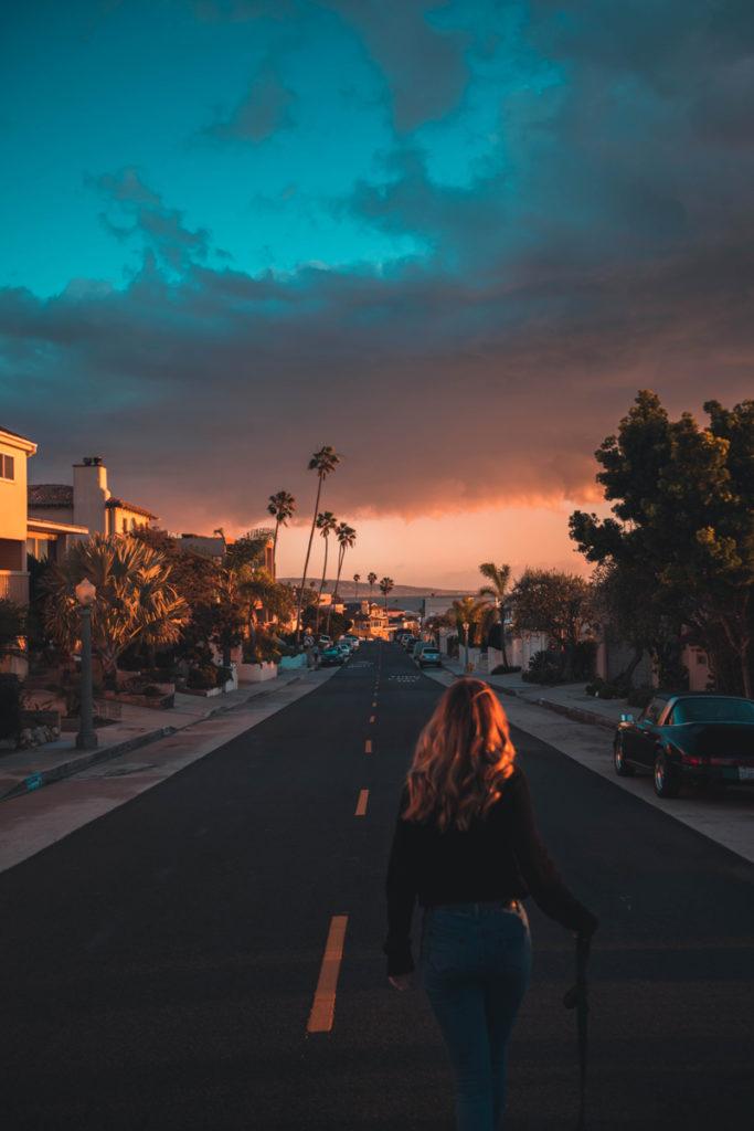 Girl walking down streets near beach at sunset