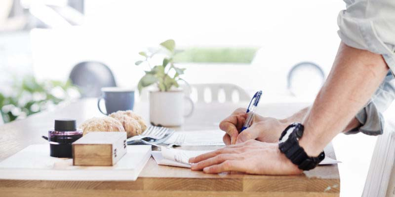 person signing document at kitchen table