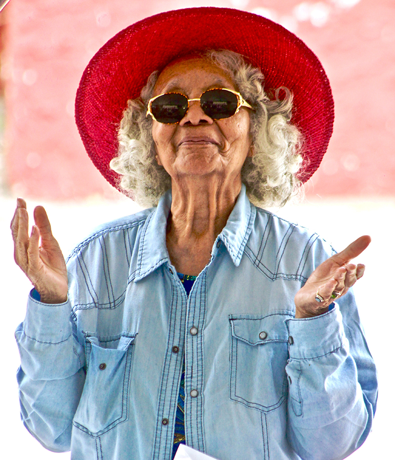 San Diego Notary, a older woman holds her hands in the air as if grateful, she wears a red sun hat outdoors