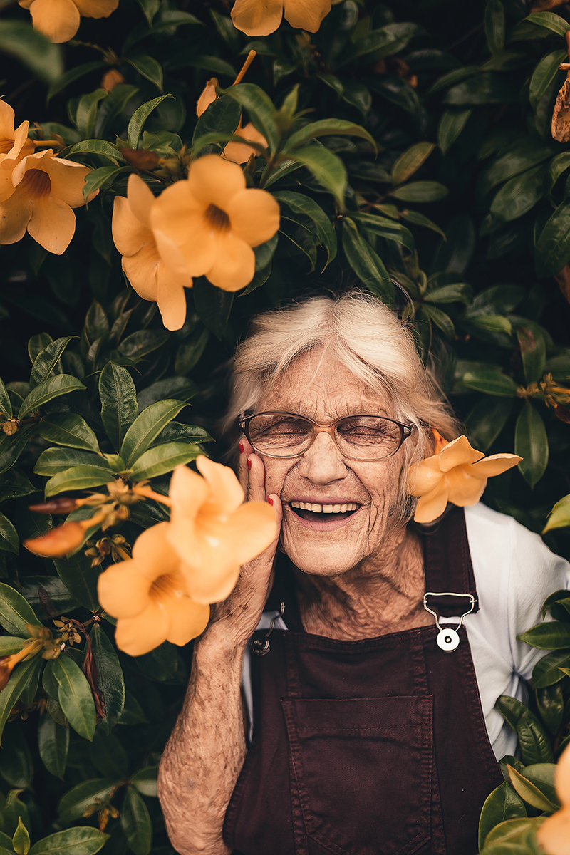 San Diego Notary, an older woman is partially standing in a large bush, she smiles as the flowers surround her